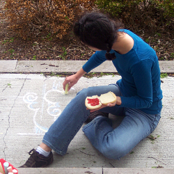 Nadia is sitting on the sidewalk creating a chalk masterpiece while holding a hamburger bun waiting for a hamburger to be insterted.