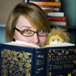 Natalie peaks playfully over the top of a Grimm's Fairy Tales book with her trusty Leo the Laundry Lion.