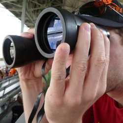 Thomas' face is obscured by bonoculars in this photo as he searches out new images to capture.