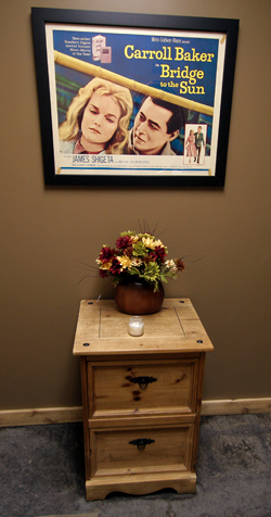 A vintage movie poster hangs above a distressed wood mini-dresser with a lovely flower arrangement on top.