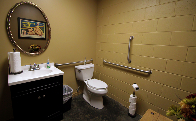 Looking into the bathroom, the photo sink, gilded oval mirror with a movie poster seen in the reflection and a toilet.