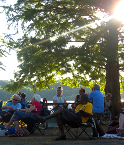 A crowd of people sit and listen while the sun sets at Eagle Creek Park.
