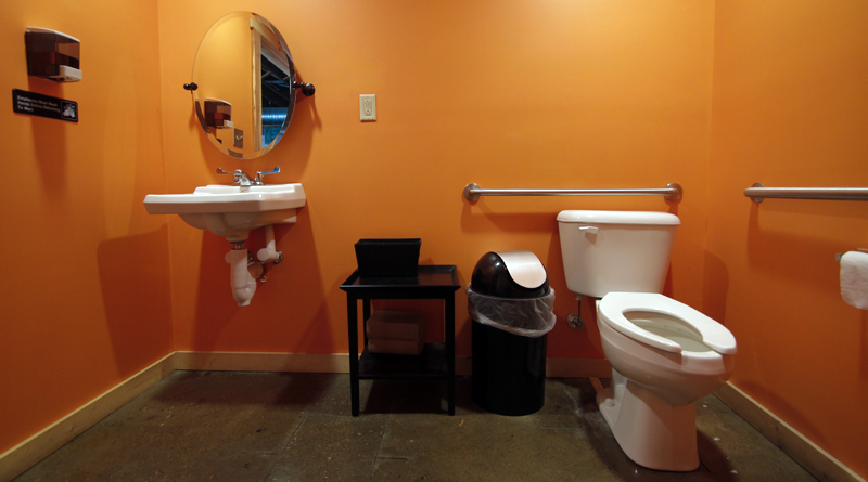 Looking into the bathroom, the photo frames sink, toilet and lovely black end table in a very bright orange room at Flat 12 Bierwerks.