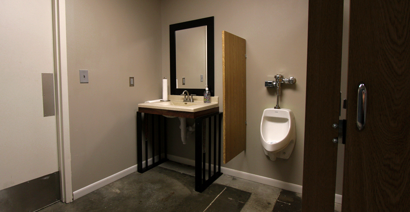 Looking into the bathroom, the photo frames sinkand urinal. Unpictured is a grand chalkboard behind the photographer.