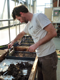 Tyler presses the soil mixture together to make seed starting blocks in the greenhouse at the Near-Eastside Legacy Center.