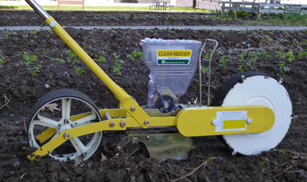 A strange yellow contraption with two wheels, a seed hopper and small plow that is a wheel seeder.