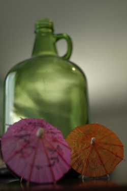 A green glass growler looms out of focus in the background with pink and yellow cocktail umbrellas  set in the foreground.