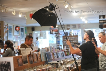 A man postitions a light above a model in a music store during a photo scoot. Photo by Esther Boston.
