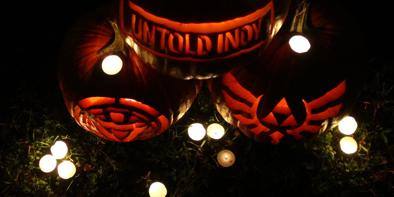 Looking down at three carved pumpkins surrounded by candles.