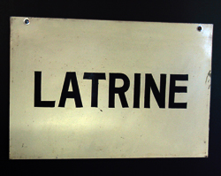 A close up of the vintage LATRINE sign.