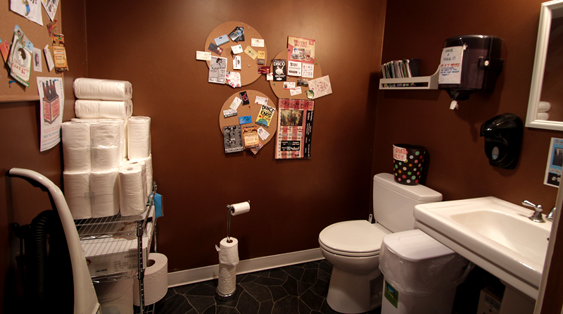 Looking into the bathroom, the photo frames sink, toilet, vacuum, and extra paper products stacked in the corner at Upland Indianapolis Tasting Room.