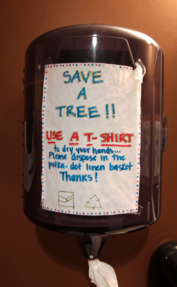 A close up on the paper towel dispenser at Upland Brewery that says Save a Tree Use a T-Shirt!